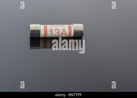 Domestic appliance electrical 13 Amp fuse (Ceramic Cartridge type) on reflective black background. Metaphor electrical safety. 25mm L x 6.3mm D - Stock Photo