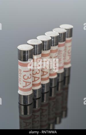 Domestic appliance electrical 13 Amp fuses (Ceramic Cartridge type) on reflective black background. Metaphor electrical safety. 25mm L x 6.3mm D - Stock Photo
