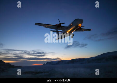 Plane coming into land at Pangnirtung Airport during a winter sunset - Stock Photo