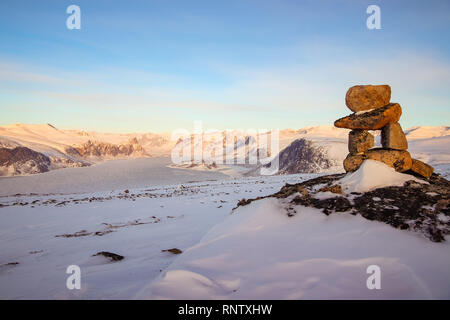 An Inukshuk which is the symbol of Nunavut, located on top of a mountain behind the hamlet of Pangnirtung on Baffin Island. - Stock Photo