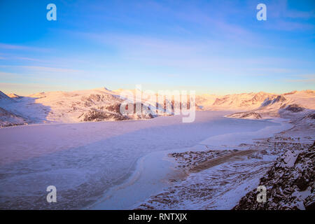 From up in the hills behind Pangnirtung are views over the frozen ice that lead through the fiord on Auyuittuq National Park. - Stock Photo