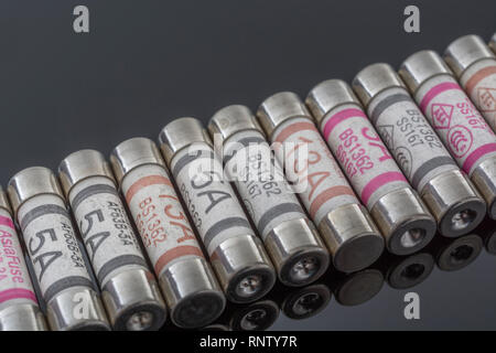 Domestic appliance 3A, 5A & 13A electrical fuses (Ceramic Cartridge type) on reflective black background. Metaphor electrical safety. 25mm L x 6.3mm D - Stock Photo