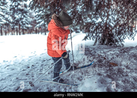 A 3-5 year old boy rides and walks alone on toy toy skis. Winter forest drifts and wood drift on background. The first steps in sport and active - Stock Photo