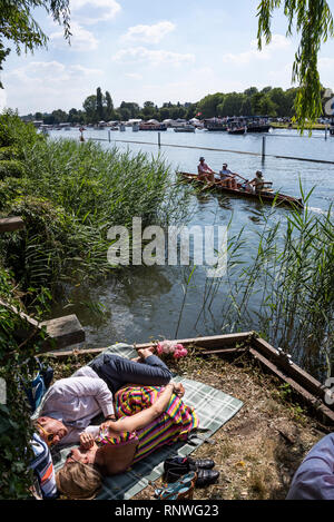A couple lie of the riverbank, Henley Royal Regatta, Henley on Thames, Oxfordshire, UK - Stock Photo