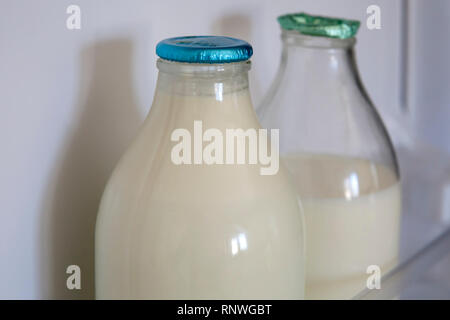 Reusable glass milk bottles are back in fashion in the UK as many consumers do their best to reduce, reuse and recycle. Whole and semi skimmed organic - Stock Photo
