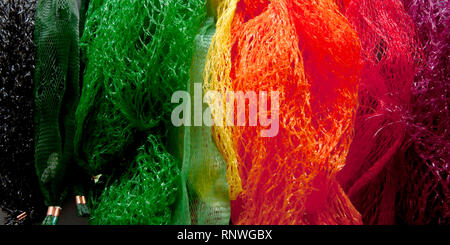 A rainbow-coloured array of plastic fruit and vegetable nets of the type labelled 'not yet recycled' in the UK, which end up in landfill or the ocean - Stock Photo