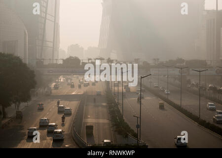 Traffic and pedestrians in hazardous levels of air pollutioN in Cyber City, Gurugram, India - Stock Photo