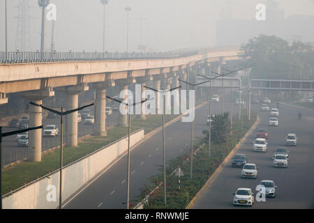 Metro train and traffic in hazardous levels of air pollution in Cyber City, Gurugram, India - Stock Photo