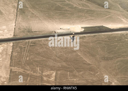 Three Nazca Lines figures (hand, tree, iguana) close to the Panamericana road and the observation tower seen from above in the desert, Nazca, Peru. - Stock Photo