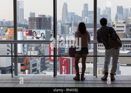 A young Japanese woman and man look out a view of Shinjuku from  large view windows in the Hikarie Tower in Shibuya, Tokyo, Japan. Thursday, October 3 - Stock Photo
