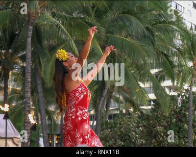 WAIKIKI, UNITED STATES OF AMERICA - AUGUST 6 2015: a female hula dancer in a red dress performing at waikiki - Stock Photo