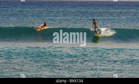 WAIKIKI, UNITED STATES OF AMERICA - AUGUST 9 2015: a young boy rides a longboard at waikiki beach - Stock Photo