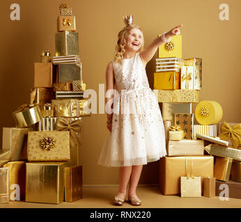 Full length portrait of smiling young girl in beige fit and flare dress and a little crown on head among 2 piles of golden gifts in front of a plain w - Stock Photo