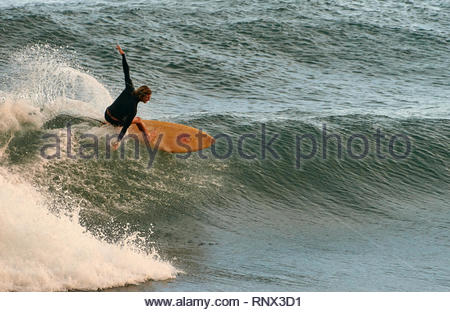 A male surfer in a wet-suit, performing a stylish 'off-the-lip' frontside cutback, on a nice green wave, during moderate swell in the shore-break. - Stock Photo