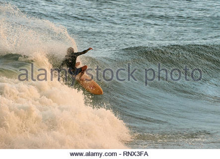 A male surfer in a wetsuit, performing an 'off-the-lip' frontside re-entry / reo - kicking up sea-spray; whilst surfing decent swell at Turners Beach. - Stock Photo