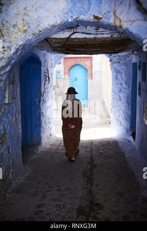 One person walking through a blue rinsed arched passageway in Chefchaouen, Morocco, Africa. - Stock Photo