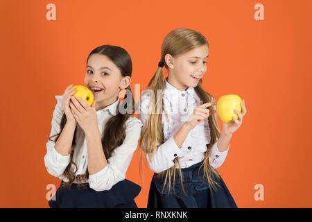 Distributing free fresh fruit at school. Girls kids school uniform orange background. Schoolgirls eat apples. School lunch. Vitamin nutrition during school day. Boost student acceptance of fruit. - Stock Photo