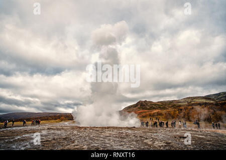Iceland. Marvel active hot spring of Strokkur spouts steaming water 30 meters People watch steam eruption Ecology, environment, nature. Tourist destination, travelling, vacation, wanderlust concept - Stock Photo