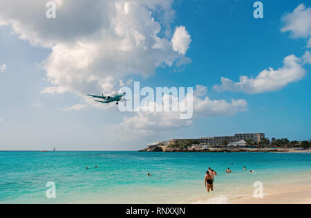 Philipsburg, Sint Maarten - February 13, 2016: plane land over maho beach. Jet flight low fly in cloudy sky. Airplane on blue sea. Beach vacation at Caribbean. Wanderlust, travel and trip. - Stock Photo