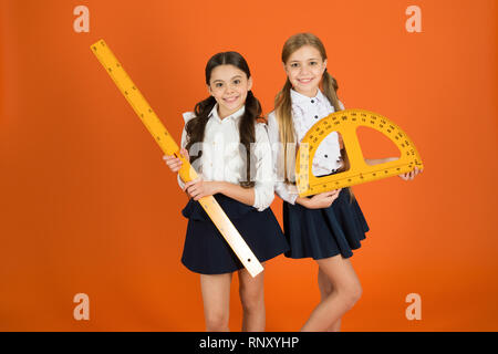 Education and school concept. School students learning geometry. Kids school uniform on orange background. STEM school disciplines. Pupil cute girls with big rulers. Geometry favorite subject. - Stock Photo