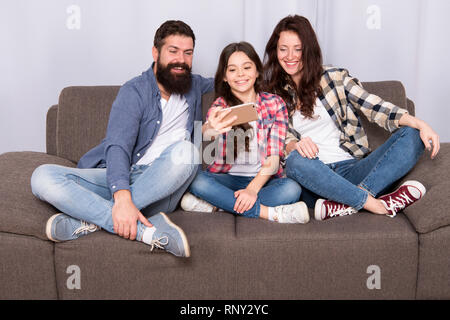Capture happy moments. Family spend weekend together. Use smartphone for selfie. Friendly family having fun together. Mom dad and daughter relaxing on couch. Family posing for photo. Family selfie. - Stock Photo