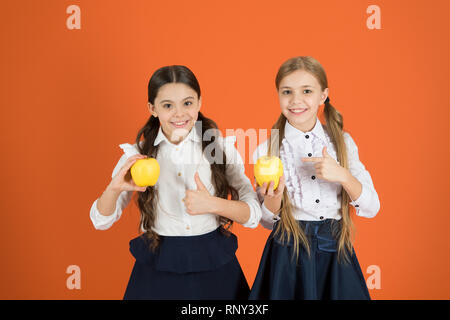 School lunch. Vitamin nutrition during school day. Boost student acceptance of fruit. Distributing free fresh fruit at school. Girls kids school uniform orange background. Schoolgirls eat apples. - Stock Photo