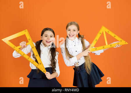 Kids school uniform on orange background. Pupil cute girls with big rulers. Geometry school subject. Drawing with ruler chalkboard. Education and school concept. School students learning geometry. - Stock Photo