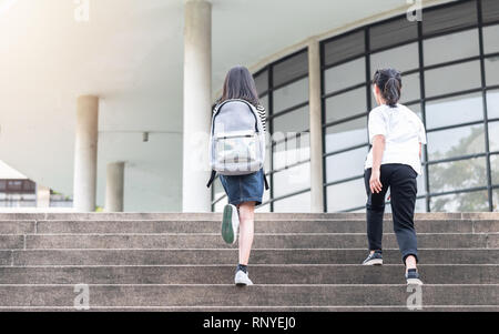 Back to school education concept with girl kids (elementary students) carrying backpacks going, running to class on school first day and walking up bu - Stock Photo