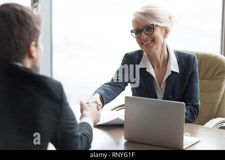 Friendly hr manager handshaking applicant hiring candidate at job interview - Stock Photo