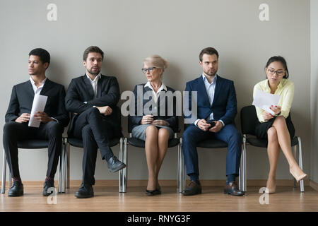 Diverse businesspeople applicants sitting in row waiting for job interview - Stock Photo