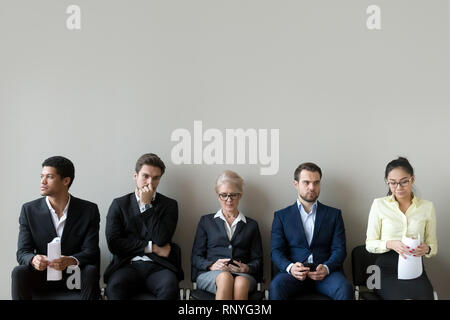 Multi-ethnic applicants sitting in row queue line preparing for interview - Stock Photo