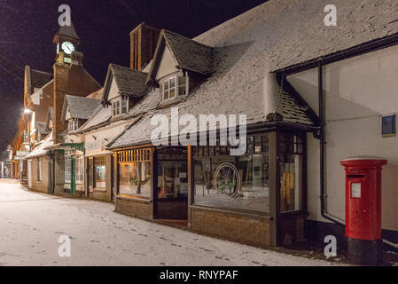 High Street in the New Forest village of Fordingbridge, Hampshire, UK after an evening winter snowfall. - Stock Photo