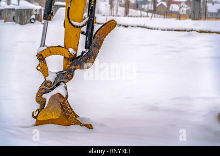 Excavator digging snow on a winter day in Utah - Stock Photo
