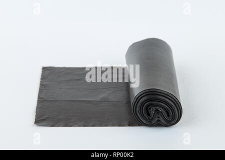 Black plastic polyethylene garbage bags roll isolated over the white background. - Stock Photo