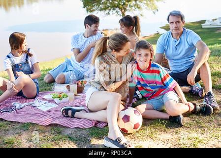 Family enjoying picnic near lake - Stock Photo
