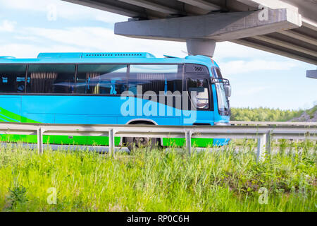 tourist bus goes on highway under bridge in country - Stock Photo