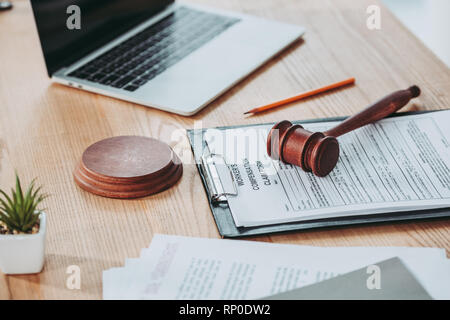 clipboard with compensation claim form and gavel lying over on the office desk, compensation concept - Stock Photo