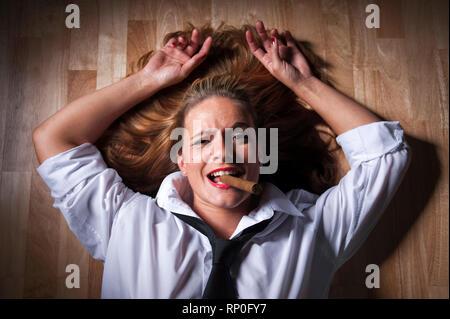 Dunkelblonde Frau mit ausgebreiteten Haaren liegt rauchend auf dem Boden. Sie traegt ein weisses Maennerhemd und eine schwarze Krawatte. MR:YES PR:YES - Stock Photo