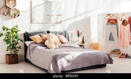 modern interior design of bedroom with teddy bear toys, pillows, plants and bed