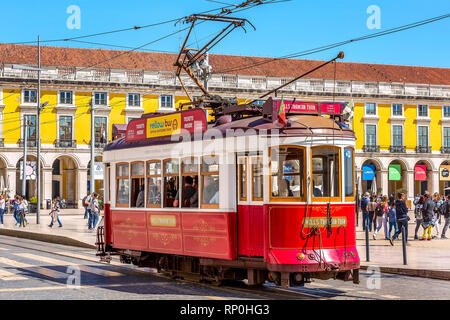 Lisbon, Portugal - March 27, 2018: Red tourist tram, symbol of Lisbon and downtown Square of commerce - Stock Photo