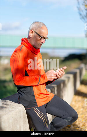 Senior runner in nature with smartphone. - Stock Photo