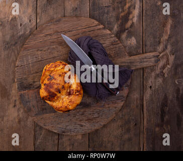Rosemary & rock salt Focaccia bread on a retro wooden bread board with a knife and napkin - Stock Photo