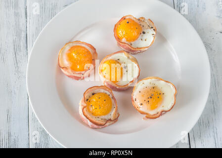 Bacon and egg cups on the white plate: top view - Stock Photo