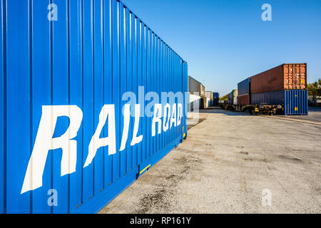 Shipping containers waiting on a railroad platform along a freight train in a river port in the suburbs of Paris, France. - Stock Photo