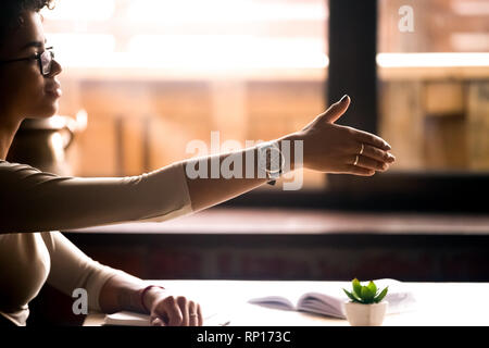 Female sitting at table holds out her hand for handshake - Stock Photo