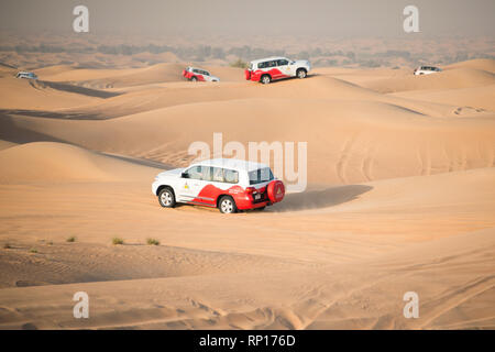 DUBAI, UAE - February 18, 2018: Desert safari - driving off-road vehicles through the sand dunes, traditional entertainment for tourists in desert clo - Stock Photo
