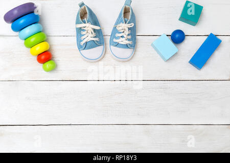 Shoes for little boy and wooden cubes on a wooden background - Stock Photo