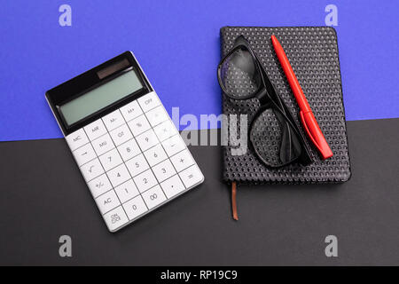 Modern workplace with notebook, pen and calculator isolated on blue black background - Stock Photo