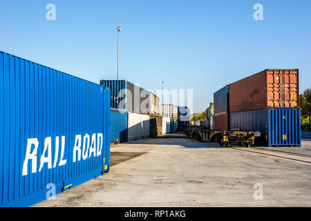 Cargo containers waiting on a railroad platform along a freight train in a river port in the suburbs of Paris, France. - Stock Photo