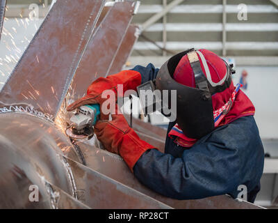Industrial worker wearing a welding mask using an angle grinder on a steel structure. - Stock Photo